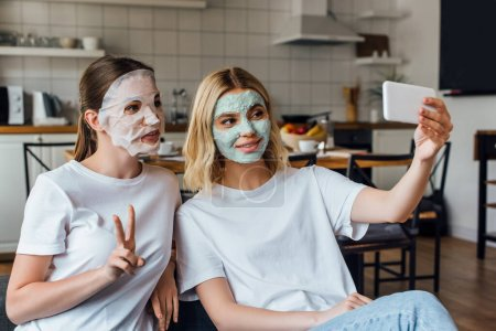 Photo for Sisters in face masks showing peace gesture and smiling while taking selfie with smartphone at home - Royalty Free Image