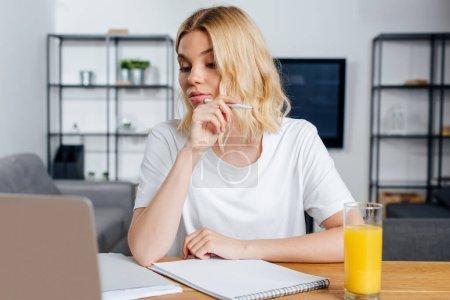 Photo pour Mise au point sélective d'un magnifique stylo indépendant près d'un ordinateur portable, de papiers et de jus d'orange sur la table à la maison - image libre de droit