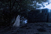 Low key image a blur white ghost under big tree in ancient fores