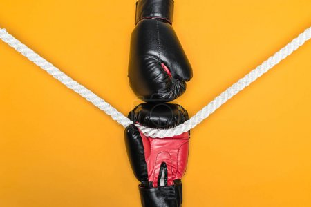 Photo for Black boxing gloves ready to fight with rope in the middle isolated on yellow - Royalty Free Image