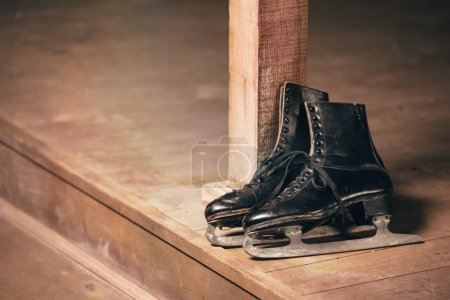Photo for Closeup view of black old ice skates lying on wooden porch - Royalty Free Image