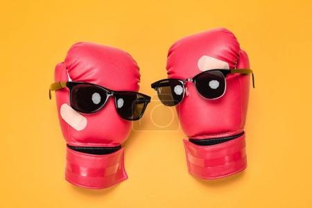 Photo pour Paire de gants de boxe rouges dans des lunettes de soleil rendant la composition souriante isolée sur jaune - image libre de droit