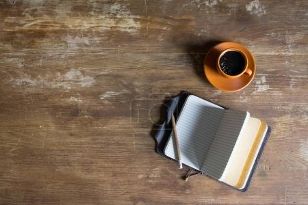 Photo for Top view of diary with pencil and coffee cup on wooden tabletop - Royalty Free Image