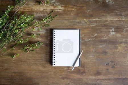 Photo pour Vue du dessus du bloc-notes avec crayon et fleurs sur table en bois - image libre de droit