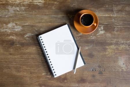 Photo for Top view of notepad with pencil and coffee cup on wooden tabletop - Royalty Free Image