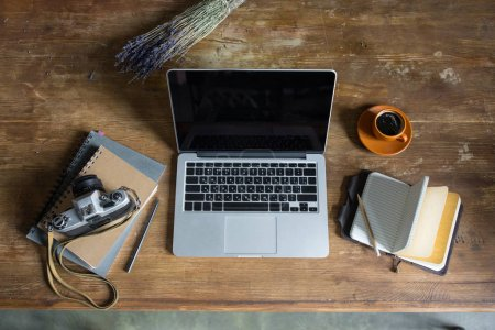 Top view of laptop, diaries, vintage photo camera and cup of coffee on wooden tabletop