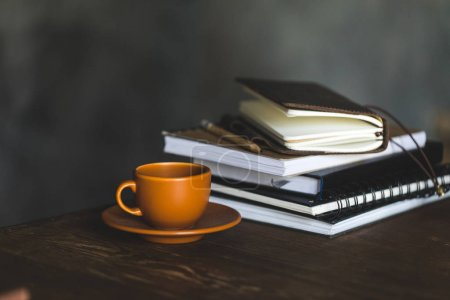 Photo for Close-up view of cup of coffee and notebooks on wooden table top - Royalty Free Image