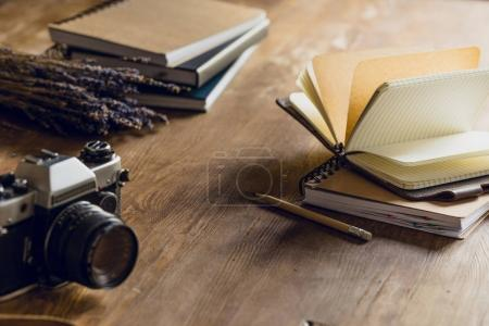 Close-up view of camera, dried flowers and notepads on wooden table