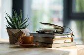 """Постер, картина, фотообои """"Крупным планом книги, записная книжка с карандашом и чашкой кофе на деревянном столе"""""""