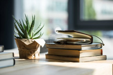 Photo for Close-up view of books, notebook with pencil and potted plant on wooden table - Royalty Free Image
