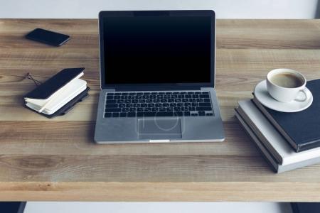 Photo pour Vue rapprochée d'ouvert ordinateur portable avec écran blanc et tasse de café au lieu de travail - image libre de droit
