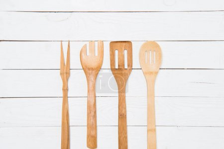 Photo for Top view of various wooden spatulas on white tabletop - Royalty Free Image