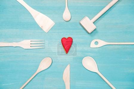 Photo pour Vue de dessus de divers ustensiles de cuisine en bois avec le symbole du coeur sur le dessus de table bleu - image libre de droit