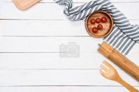 Photo for Cherry tomatoes with wooden spatula and salt grinder with table cloth on tabletop - Royalty Free Image