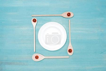 Top view of wooden spoons with cherry tomatoes and empty white plate on table
