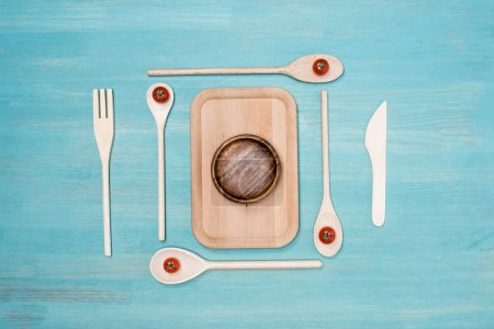 Top view of wooden cutting board with kitchen utensils and cherry tomatoes on table