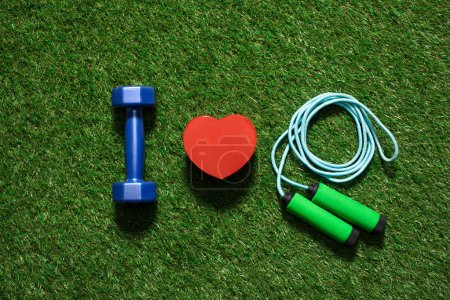 Photo for Top view of colorful dumbbell with heart symbol and skipping rope on the grass - Royalty Free Image