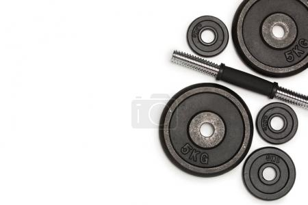 Top view of heavy weight plates with iron bar isolated on white