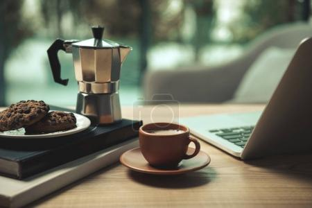 Photo for Close-up view of laptop, cup of coffee, moka pot and chocolate chip cookies with books on wooden table - Royalty Free Image