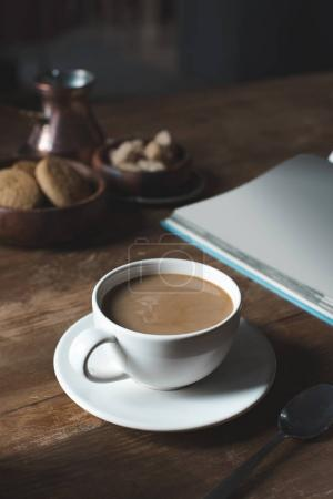 Photo for Close up of coffee cup with empty book on wooden tabletop - Royalty Free Image
