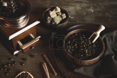 coffee grinder with beans on wooden tabletop