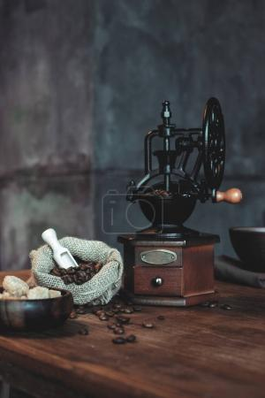 Photo for Vintage coffee grinder with beans and brown sugar in bowls on wooden tabletop - Royalty Free Image