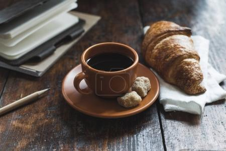 Photo for Coffee with croissant on cloth and notebooks with pencil on wooden tabletop - Royalty Free Image