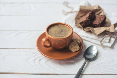 Coffee with brown sugar and spoon on tabletop