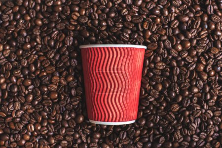 Plastic cup on roasted coffee beans