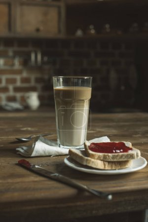 latte and bread with jam on wooden tabletop