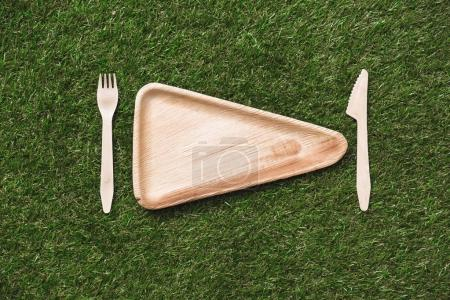 Photo for Top view of triangular plate with wooden fork and knife on grass - Royalty Free Image