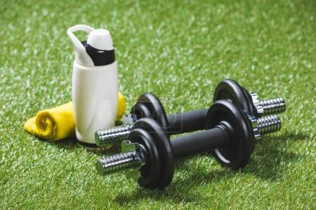 dumbbells and bottle of water with towel on grass