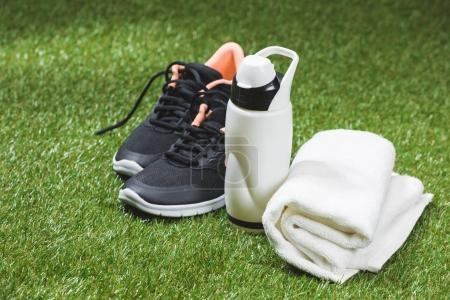 trainers with bottle of water and towel on pitch