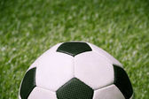 soccer ball on green football pitch