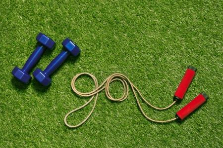 Dumbbells with jump rope on grass