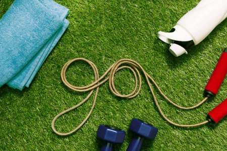 Springseil mit Handtuch und Flasche auf Gras