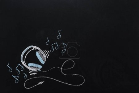headphones with musical notes drawn on chalkboard