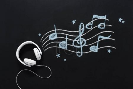 Photo for Headphones with wire and musical notes drawn on black chalkboard - Royalty Free Image