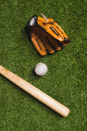 baseball bat with ball and glove on grass