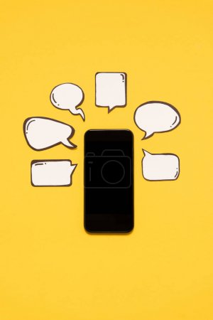 Photo for Close-up view of smartphone with black screen and blank speech bubbles isolated on yellow - Royalty Free Image