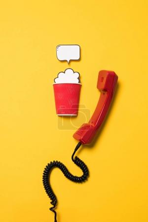 Photo for Close-up view of classic telephone handset and paper cup with speech bubble isolated on yellow - Royalty Free Image