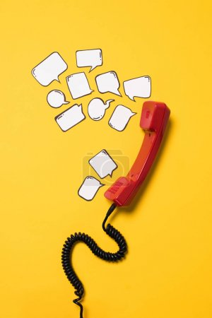 Photo for Close-up view of red telephone handset and blank speech bubbles isolated on yellow - Royalty Free Image
