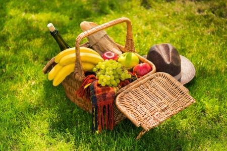 Photo pour Vue rapprochée du panier pique-nique en osier avec fruits et vin, plaid et chapeau sur pelouse verte - image libre de droit