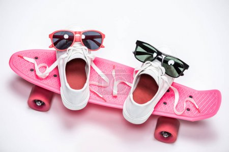 Photo for Sneakers with sunglasses standing on pink skateboard isolated on white - Royalty Free Image