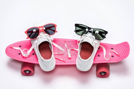 Sneakers and sunglasses on skateboard