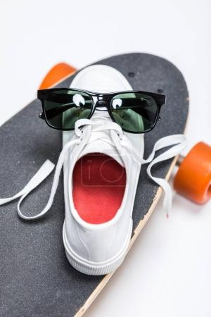 Photo for Close up view of sneaker with sunglasses standing on skateboard isolated on white - Royalty Free Image