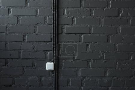 Photo for Electrical switch and wires on black brick wall background - Royalty Free Image