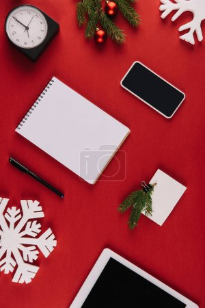 flat lay with office supplies, decorative snowflake and christmas toys isolated on red
