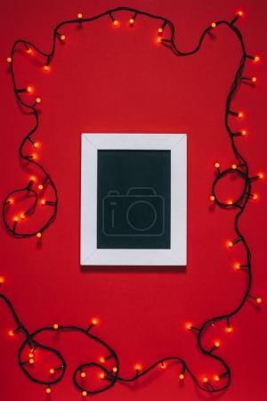top view of empty frame and christmas lights isolated on red