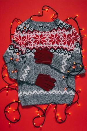 top view of winter sweater, mittens and christmas lights isolated on red